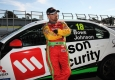 John Bowe leaning against Wilson Security Car with Fastrack V8 Supercar at Sandown Raceway